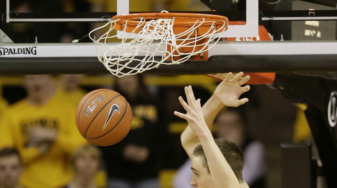 Iowa forward Nicholas Baer dunks over Michigan State guard Matt McQuaid (20) during the first half of an NCAA college basketball game Tuesday, Dec. 29, 2015, in Iowa City, Iowa. (AP Photo/Charlie Neibergall)