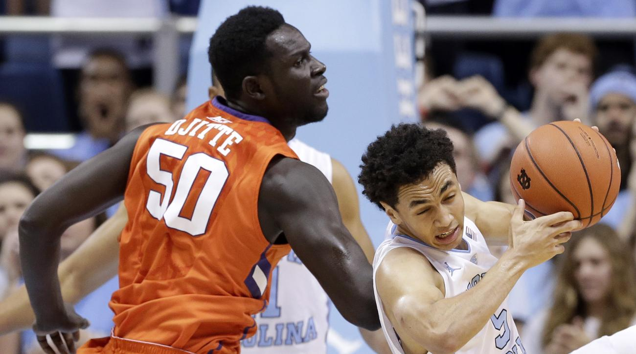 North Carolina's Marcus Paige, right, pulls down a rebound against Clemson's Sidy Djitte (50) during the first half of an NCAA college basketball game in Chapel Hill, N.C., Wednesday, Dec. 30, 2015. (AP Photo/Gerry Broome)