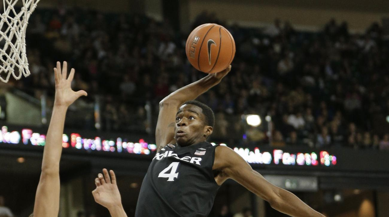 Xavier's Edmond Sumner (4) dunks against Wake Forest's Cornelius Hudson (25) and Konstantinos Mitoglou (44) in the second half of an NCAA college basketball game in Winston-Salem, N.C., Tuesday, Dec. 22, 2015. Xavier won 78-70. (AP Photo/Chuck Burton)
