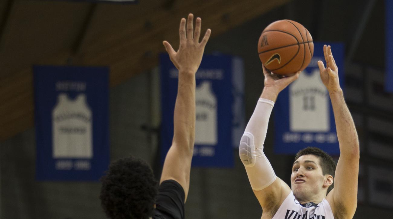 Villanova guard Ryan Arcidiacono (15) takes a 3-point shot over Xavier forward Kaiser Gates (22) in the second half of an NCAA college basketball game, Thursday, Dec. 31, 2015, in Villanova, Pa. Villanova won 95-64. (AP Photo/Laurence Kesterson)