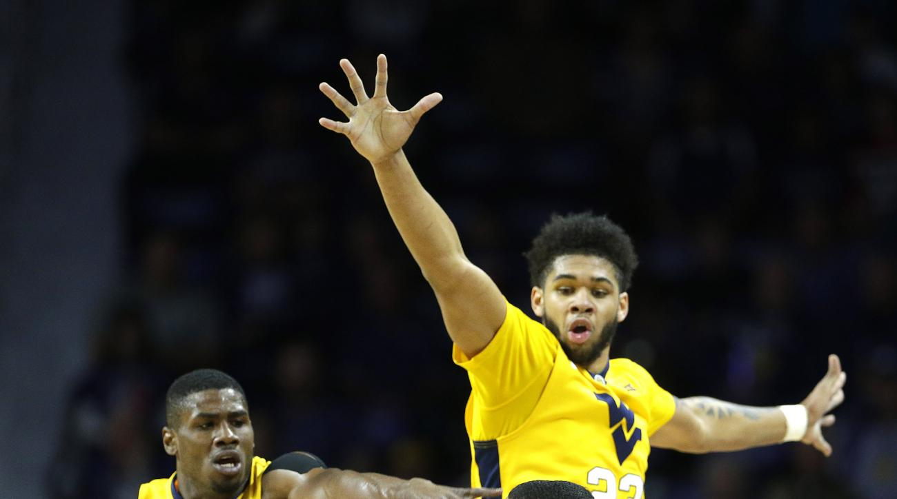 Kansas State's Justin Edwards is pressured by West Virginia's Jonathan Holton (1) and Esa Ahmad (23) during the first half of an NCAA college basketball game, Saturday, Jan. 2, 2016, in Manhattan, Kan. (AP Photo/Charlie Riedel)