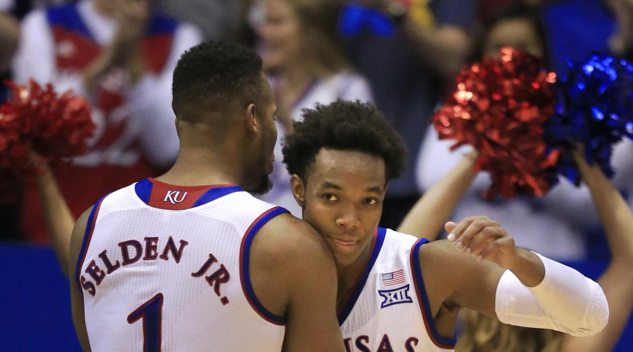 Kansas guard Devonte' Graham (4) is congratulated by teammate Wayne Selden Jr. (1) following a basket during the second half of an NCAA college basketball game against Baylor in Lawrence, Kan., Saturday, Jan. 2, 2016. Kansas defeated Baylor 102-74. (AP Ph