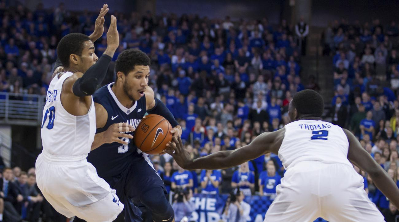 Villanova guard Josh Hart (3) tries to dribble between Creighton guards Maurice Watson Jr. and Khyri Thomas (2) during the first half of an NCAA college basketball game in Omaha, Neb., Saturday, Jan. 2, 2016. (AP Photo/John Peterson)