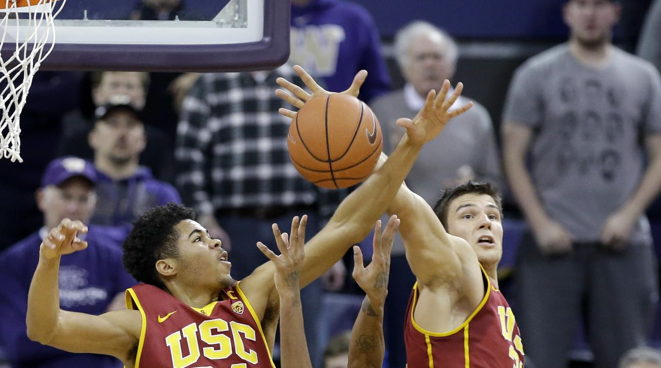 Washington's Dejounte Murray (5) tries to shoot between Southern California's Malik Marquetti (24) and Nikola Jovanovic during the second half of an NCAA college basketball game Sunday, Jan. 3, 2016, in Seattle. (AP Photo/Elaine Thompson)