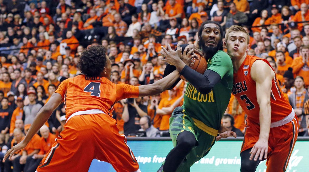 Oregon's Dwanye Benjamin, center, drives between Oregon State's Derrick Bruce, left, and Tres Tinkle, right, in the first half of an NCAA college basketball game in Corvallis, Ore., Sunday, Jan. 3, 2016. (AP Photo/Timothy J. Gonzalez)