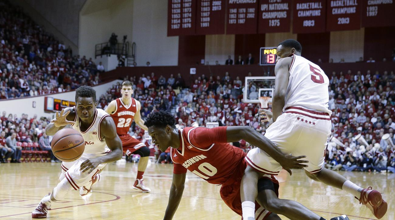 Indiana's Yogi Ferrell (11) controls a loose ball as Wisconsin's Nigel Hayes (10) and Troy Williams (5) watches during the first half of an NCAA college basketball game Tuesday, Jan. 5, 2016, in Bloomington, Ind. (AP Photo/Darron Cummings)