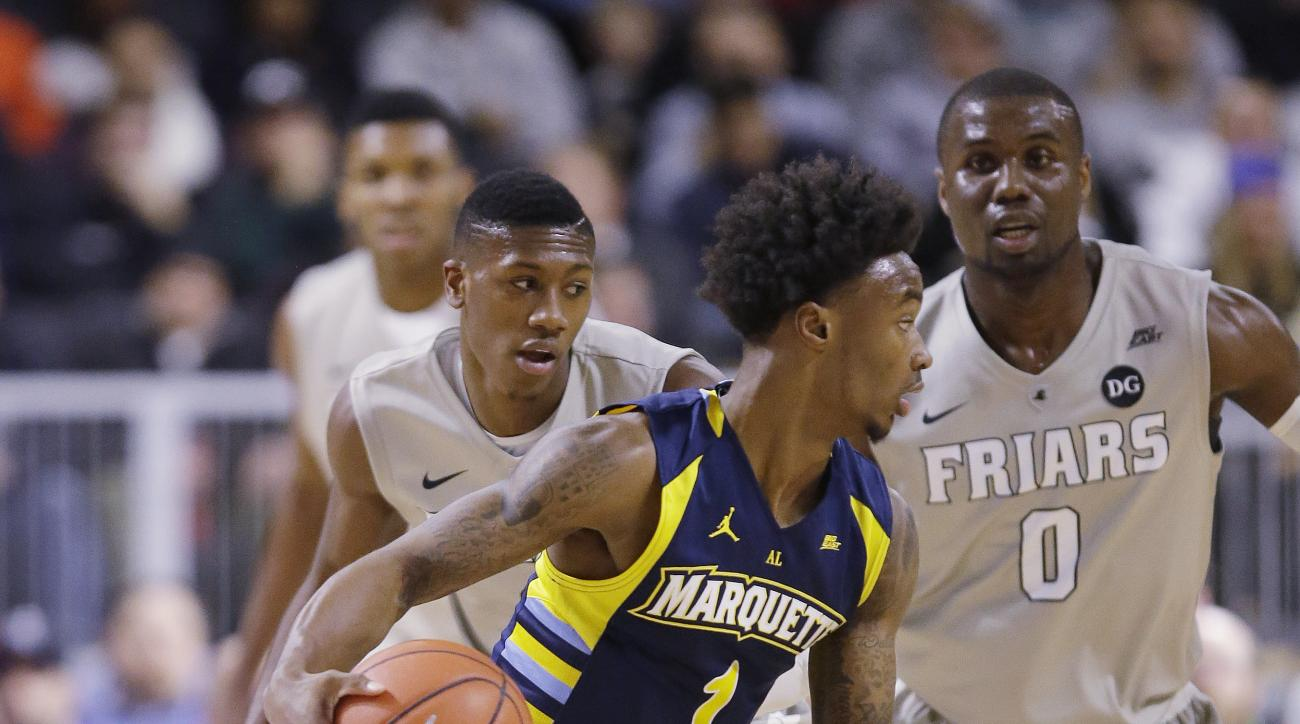 Marquette center Matt Heldt (12) looks to move to the basket against Providence guard Kris Dunn (3) and forward Ben Bentil (0) during the first half of an NCAA college basketball game, Tuesday, Jan. 5, 2016, in Providence, R.I. (AP Photo/Stephan Savoia)