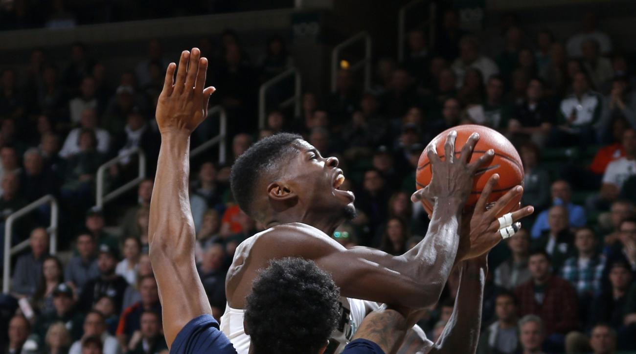 Michigan State's Eron Harris, center, goes up for a driving shot and draws a foul by Illinois' Jaylon Tate (1) during the first half of an NCAA college basketball game Thursday, Jan. 7, 2016, in East Lansing, Mich. (AP Photo/Al Goldis)