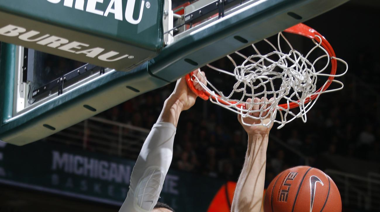 FILE - In this Dec. 9, 2015, file photo, Michigan State's Denzel Valentine dunks against Maryland-Eastern Shore during the first half of an NCAA college basketball game,  in East Lansing, Mich. Michigan State's medical staff has given Valentine the OK to