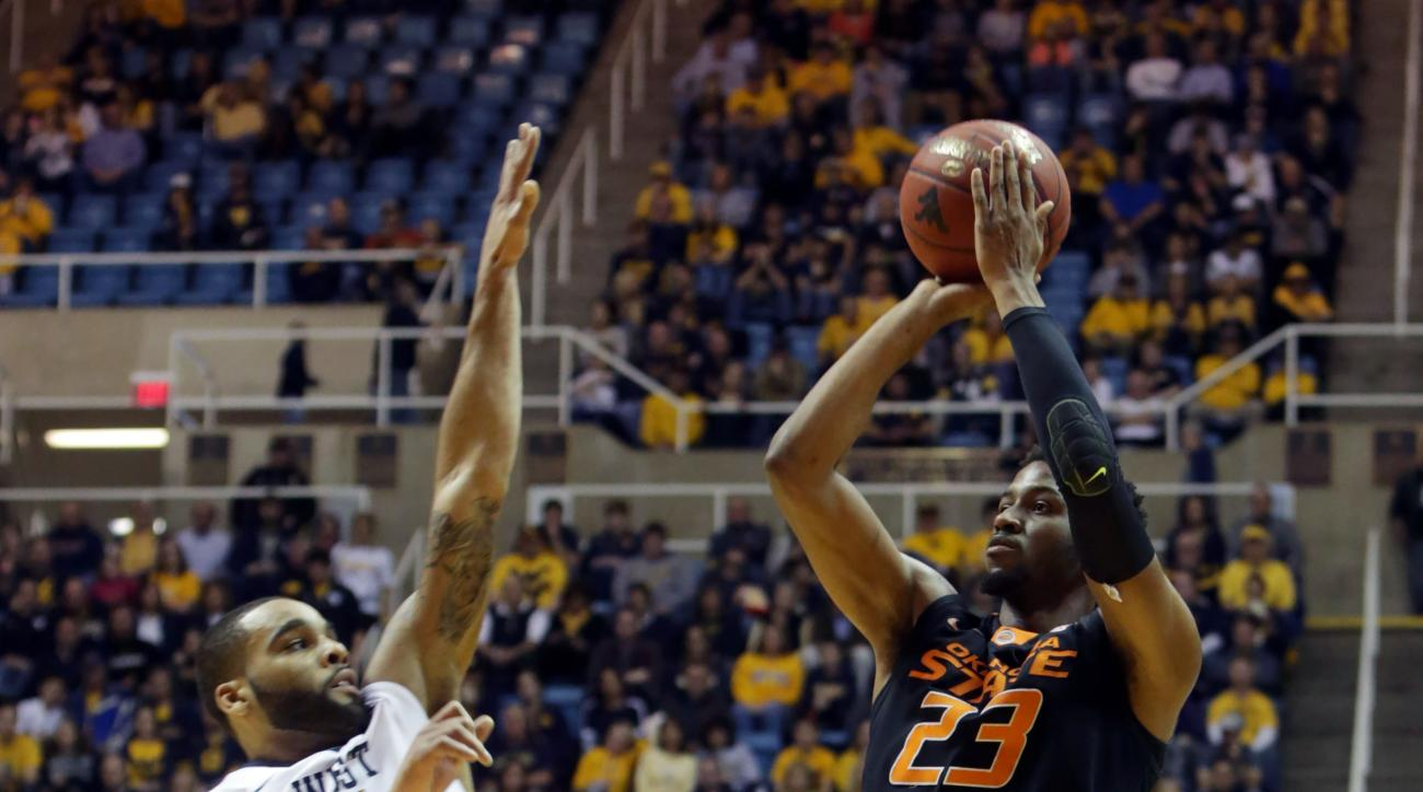 Oklahoma State guard Leyton Hammonds (23) takes a shot as West Virginia guard Jaysean Paige (5) defends during the first half of an NCAA college basketball game, Saturday, Jan, 9, 2016, in Morgantown, W.Va. (AP Photo/Raymond Thompson)