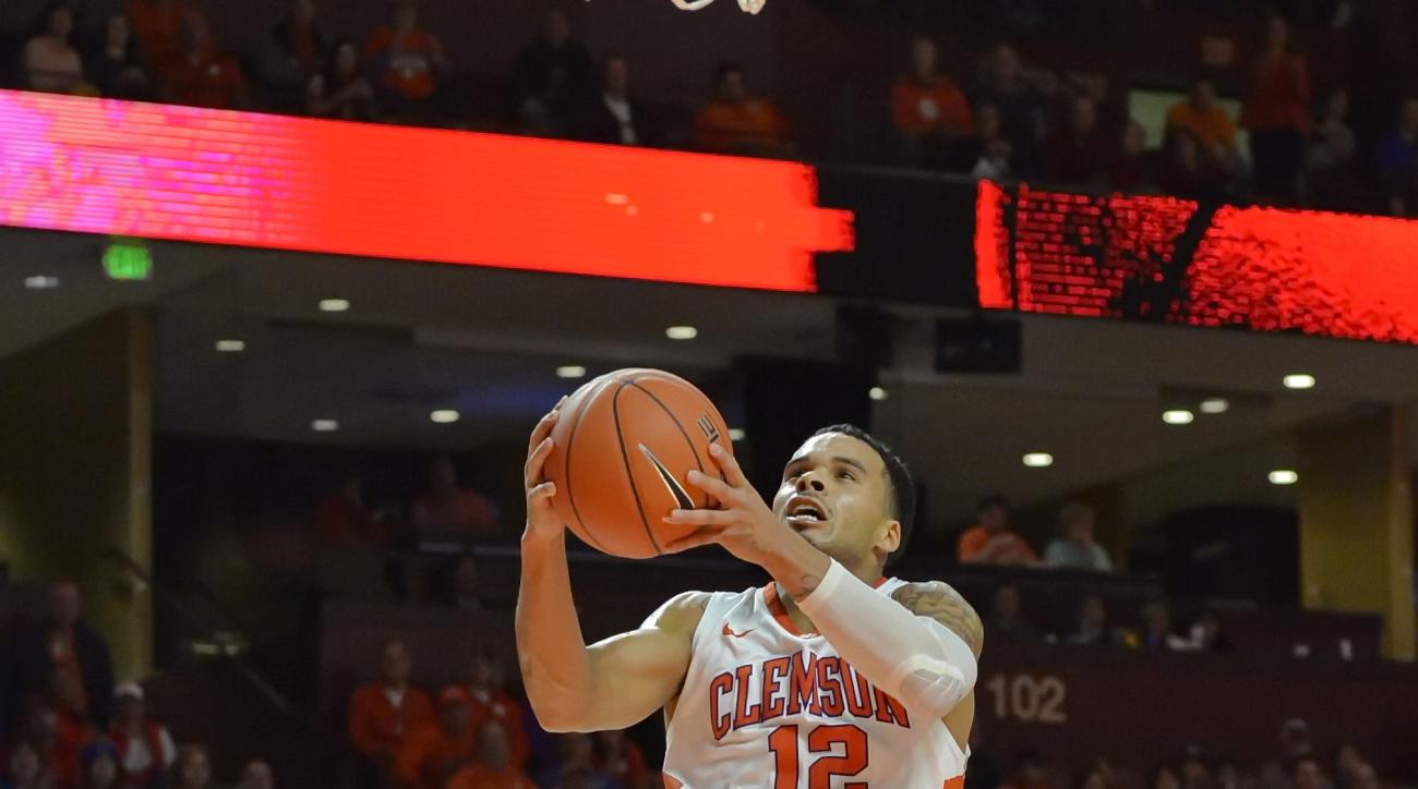 Clemson's Lyle Davis drives in for a layup while defended by Louisville's Trey Lewis during the first half of an NCAA college basketball game Sunday, Jan. 10, 2016, in Greenville, S.C. (AP Photo/Richard Shiro)