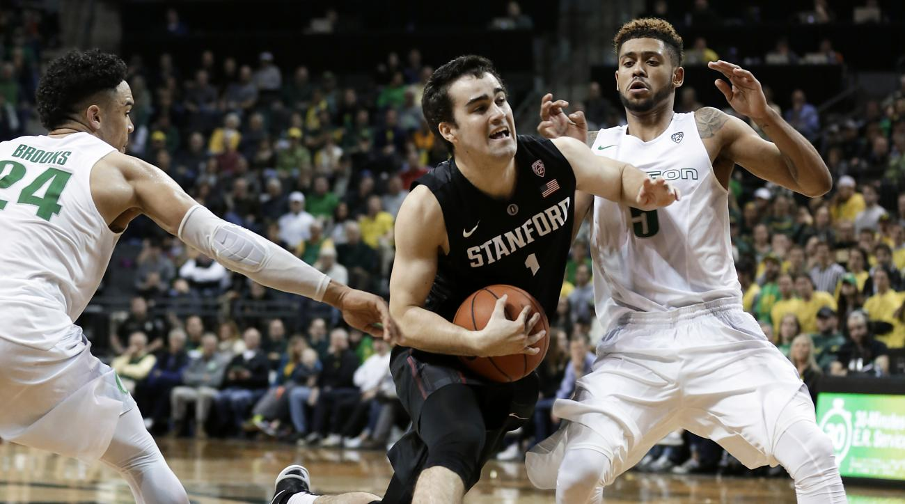Stanford's Christian Sanders, middle, drives between Oregon's Dillon Brooks, left, and Tyler Dorsey during the second half of an NCAA college basketball game Sunday, Jan. 10, 2016, in Eugene, Ore. Oregon won 71-58. (AP Photo/Ryan Kang)