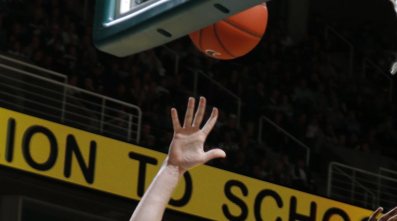 FILE - In this Nov. 20, 2015, file photo, Michigan State's Colby Wollenman, left, shoots against Arkansas-Pine Bluff's JoVaughn Love, right,  during the first half of an NCAA college basketball game,  in East Lansing, Mich. While the fourth-ranked Michiga