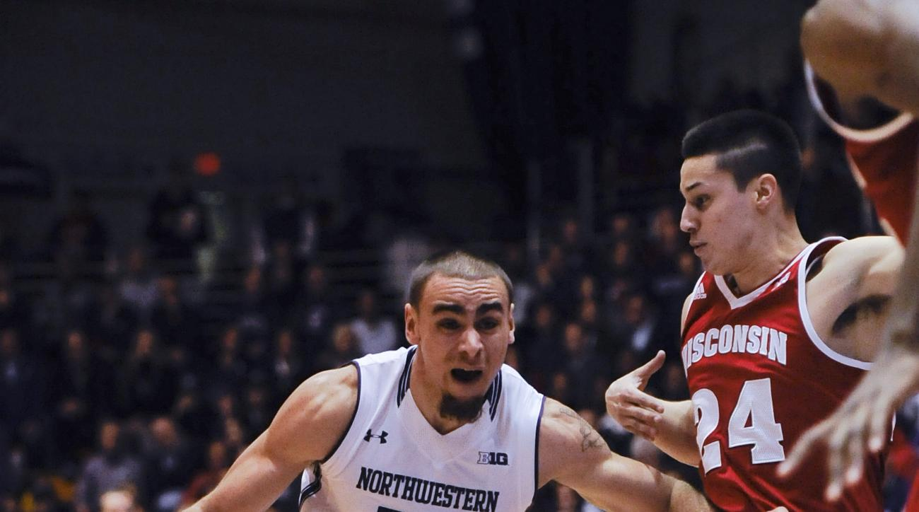 Northwestern guard Tre Demps (14) drives to the basket against Wisconsin guard Bronson Koenig (24) during the first half of an NCAA college basketball game, Tuesday,  Jan. 12,  2016. in Evanston, Ill.  (AP Photo/Matt Marton)