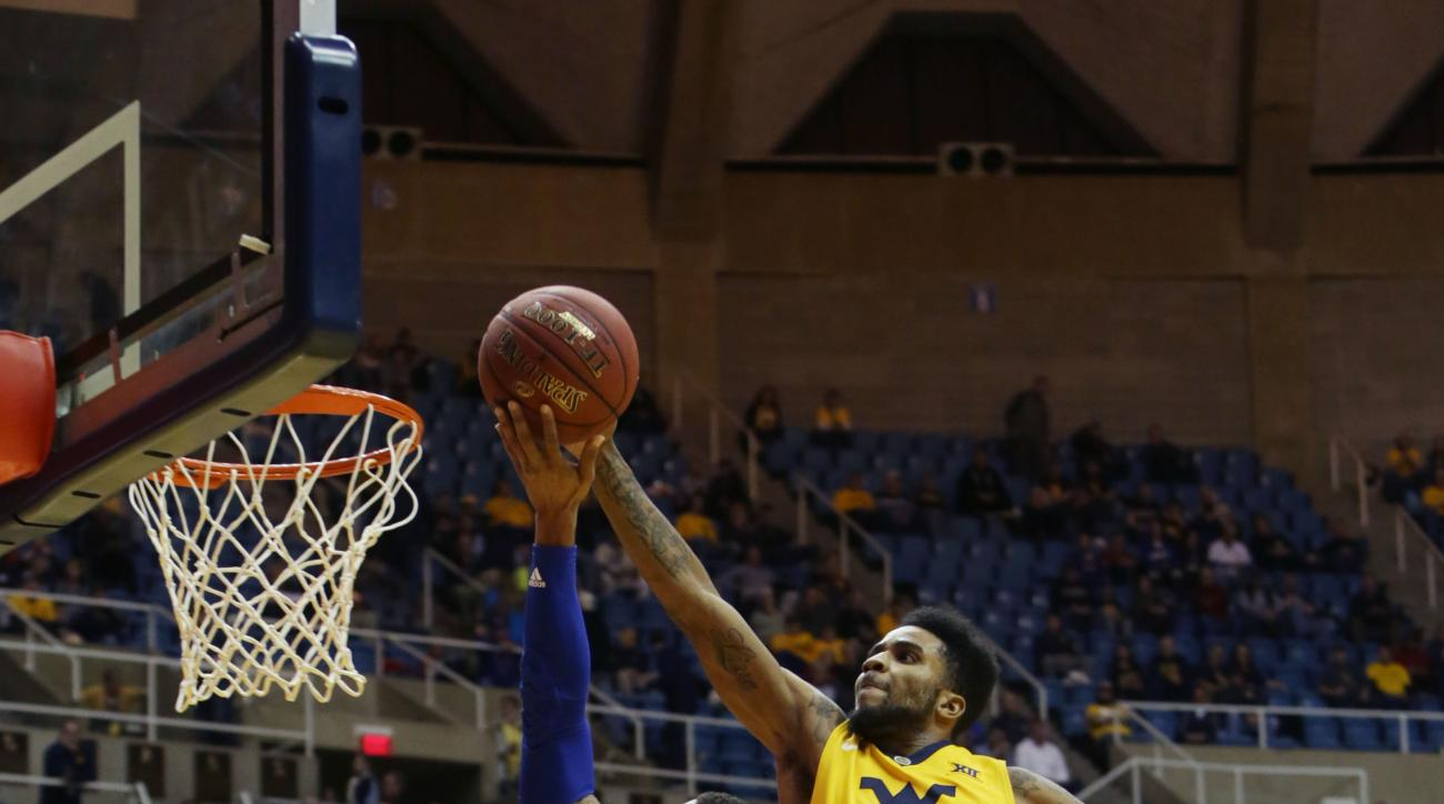 West Virginia guard Tarik Phillip (12) fouls Kansas guard Frank Mason III (0) as he drives to the basket during the first half of an NCAA college basketball game, Tuesday, Jan. 12, 2016, in Morgantown, W.Va. (AP Photo/Raymond Thompson)