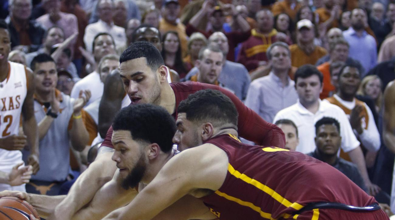 Texas guard Javan Felix, left, fights for the ball with Iowa State forward Georges Niang, right, and Abdel Nader, rear, during the second half of an NCAA college basketball game, Tuesday, Jan. 12, 2016, in Austin, Texas. Texas won 94-91. (AP Photo/Michael