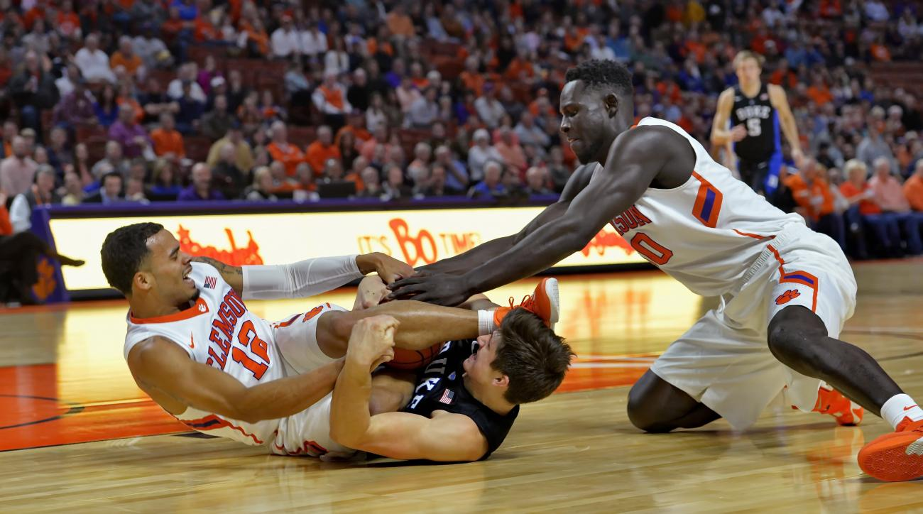 Duke's Grayson Allen, center, struggles with Clemson's Avry Holmes, left, and Sidy Djitte for a loose ball during the first half of an NCAA college basketball game Wednesday, Jan. 13, 2016, in Greenville, S.C. (AP Photo/Richard Shiro)