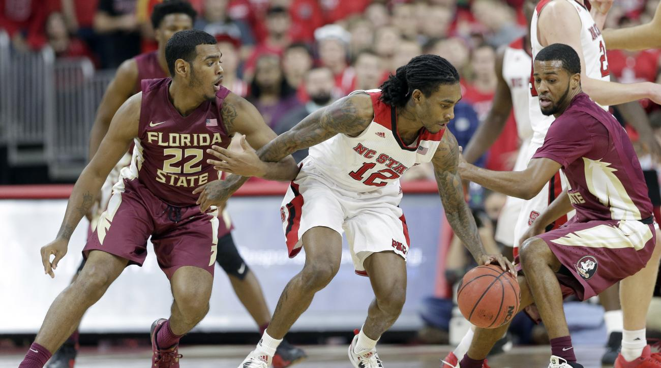 Florida State's Xavier Rathan-Mayes (22) and Devon Bookert, right, guard North Carolina State's Anthony Barber (12) during the second half of an NCAA college basketball game in Raleigh, N.C., Wednesday, Jan. 13, 2016. Florida State won 85-78. (AP Photo/Ge