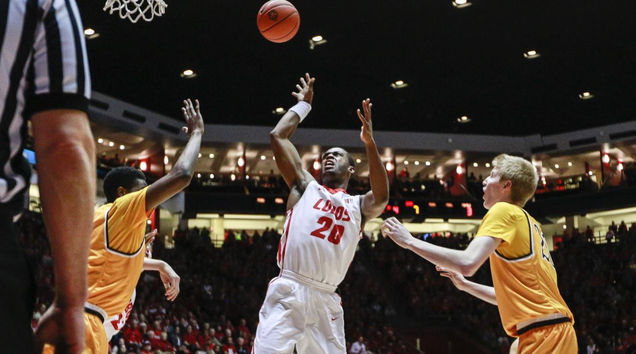 New Mexico's Sam Logwood (20) is fouled by Wyoming's Jason McManamen (23), bottom left, as he drives to the basket during the first half an NCAA college basketball game, Saturday, Jan. 16, 2016, in Albuquerque, N.M. (AP Photo/Juan Labreche)
