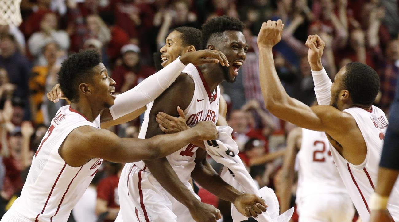 Oklahoma forward Khadeem Lattin, center, celebrates with teammates Christian James, left, Isaiah Cousins, second from left, and Jordan Woodard, right, after Oklahoma defeated West Virginia in an NCAA college basketball game in Norman, Okla., Saturday, Jan