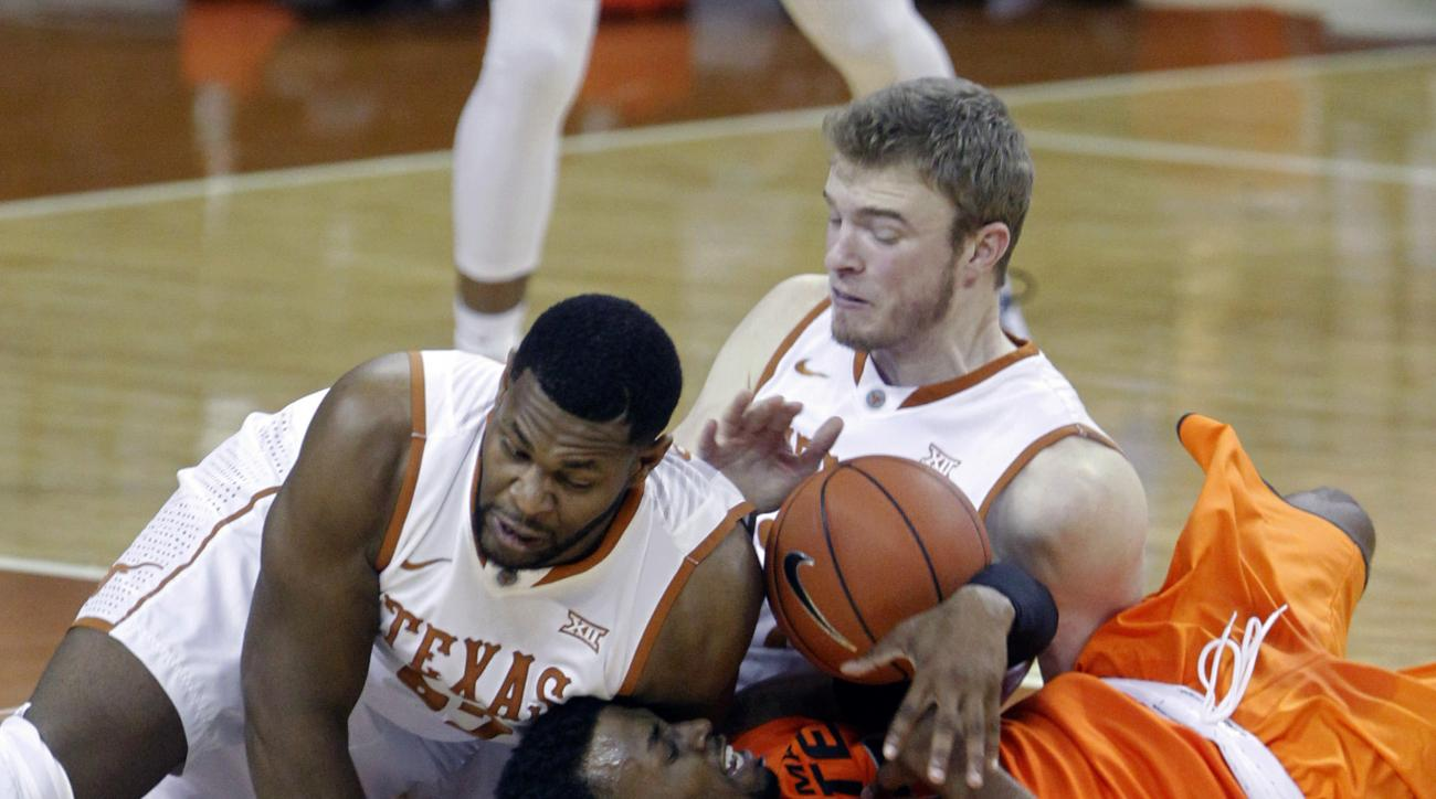 Oklahoma State forward Leyton Hammonds, center, fights for the ball with Texas forward Shaquille Cleare, left, and forward Connor Lammert, right, during the first half of an NCAA college basketball game, Saturday, Jan. 16, 2016, in Austin, Texas. (AP Phot