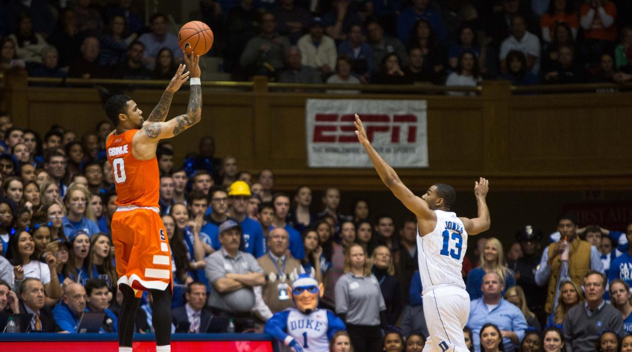 Syracuse's Michael Gbinije (0) attempts a three-point shot as Duke's Matt Jones (13) defends during the second half of an NCAA college basketball game at Cameron Indoor Stadium in Durham, N.C., Monday, Jan. 18, 2016. Syracuse defeated Duke 64-62. (AP Phot