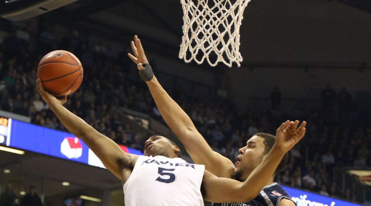 Xavier guard Trevon Bluiett (5) puts up a shot against Georgetown center Bradley Hayes (42) during the first half of an NCAA college basketball game Tuesday, Jan. 19, 2016, in Cincinnati. (AP Photo/Gary Landers)