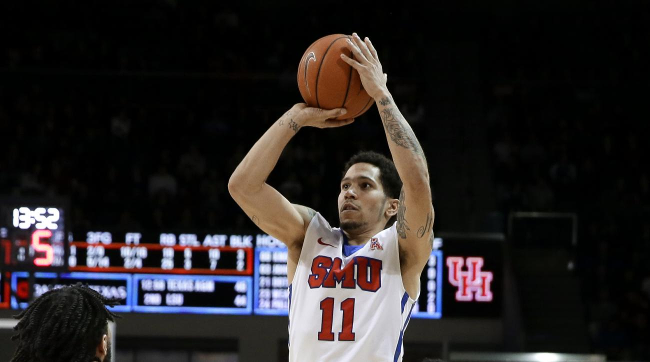 SMU's Nic Moore (11) goes up for a shot between Houston's Eric Weary Jr. (23) and Ronnie Johnson, right, in the second half of an NCAA college basketball game, Tuesday, Jan. 19, 2016, in Dallas. SMU won 77-73. (AP Photo/Tony Gutierrez)