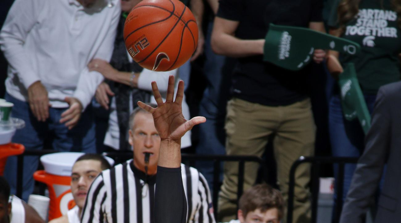 Nebraska's Shavon Shields (31) shoots against Michigan State's Matt Costello (10) and Javon Bess, right, during the first half of an NCAA college basketball game, Wednesday, Jan. 20, 2016, in East Lansing, Mich. (AP Photo/Al Goldis)