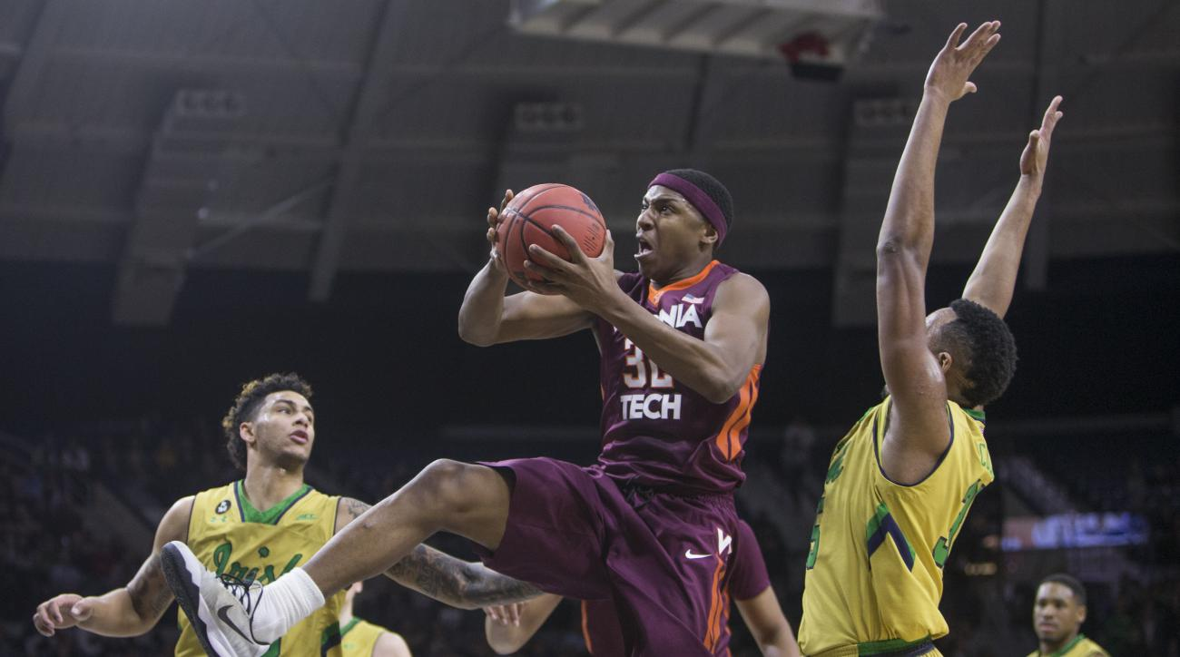Virginia Tech's Zach LeDay (32) goes up for a shot between Notre Dame's Zach Auguste (30) and Bonzie Colson (35) during the first half of an NCAA college basketball game Wednesday, Jan. 20, 2016, in South Bend, Ind.  (AP Photo/Robert Franklin)