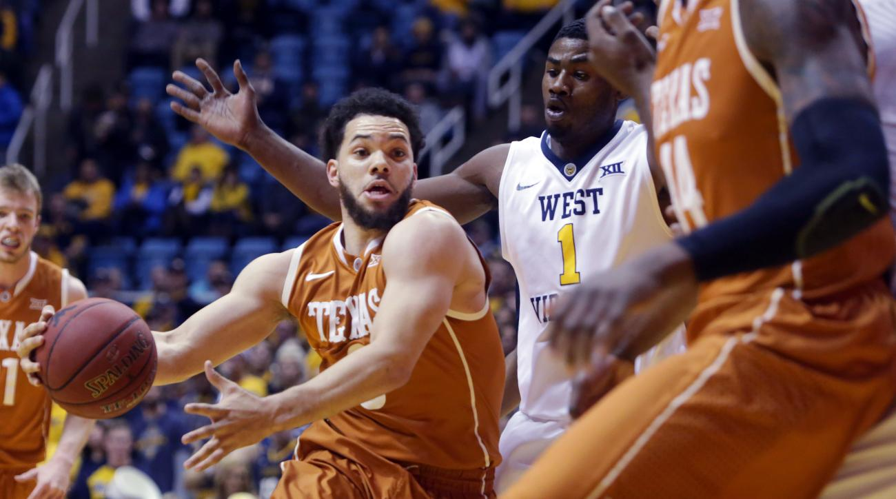 Texas guard Javan Felix (3) drives past West Virginia forward Jonathan Holton (1) during the first half of an NCAA college basketball game, Wednesday, Jan, 20, 2016, in Morgantown, W.Va. (AP Photo/Raymond Thompson)