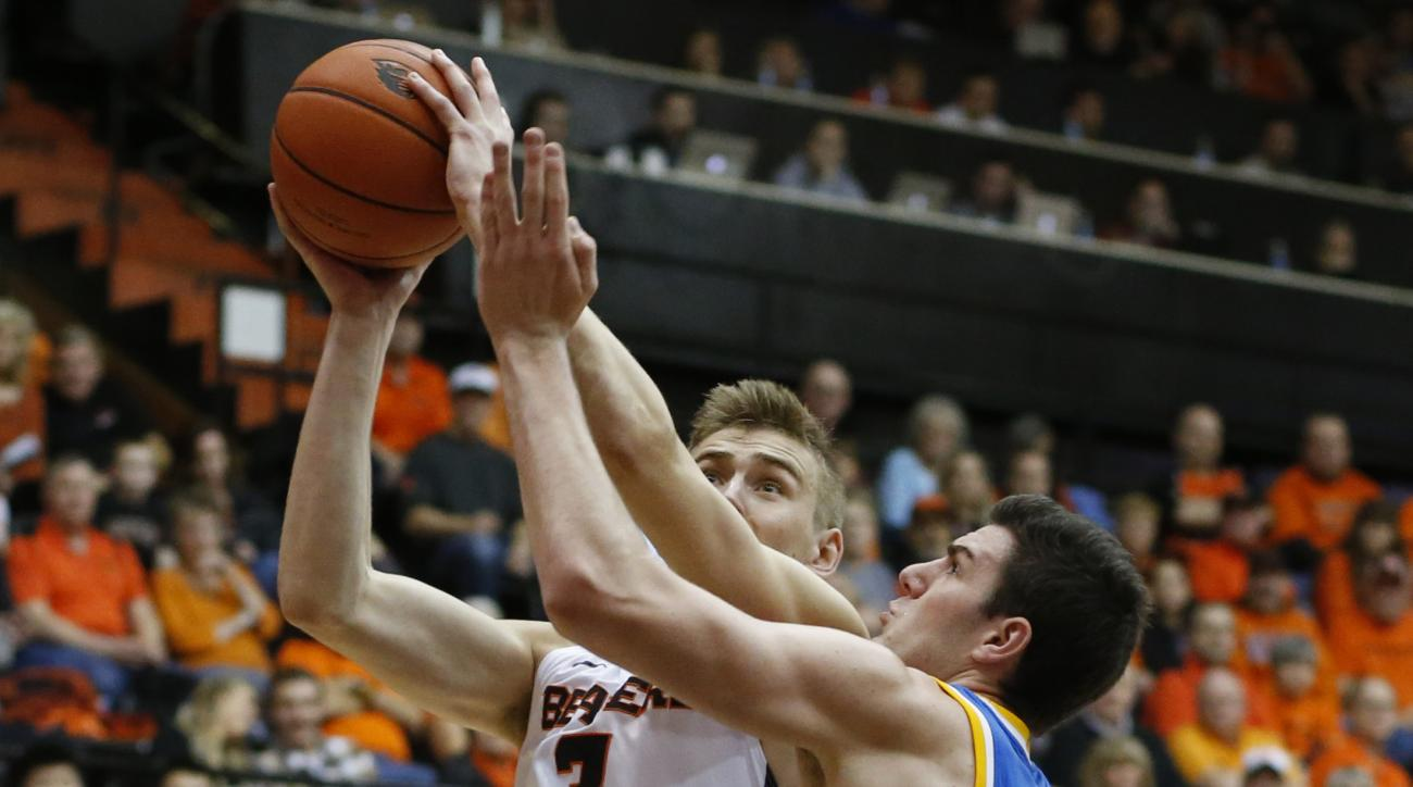Oregon State's Tres Tinkle, left, drives to the basket on UCLA's G.G. Goloman during the first half of an NCAA college basketball game in Corvallis, Ore., on Wednesday, Jan. 20, 2016. (AP Photo/Timothy J. Gonzalez)