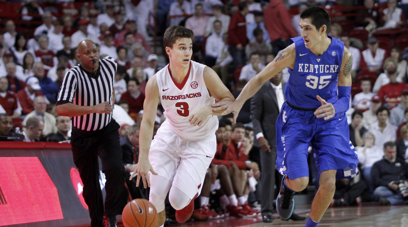 Arkansas' Dusty Hannahs (3) runs downcourt with Kentucky's Derek Willis (35) at his side during the first half of an NCAA college basketball game Thursday, Jan. 21, 2016, in Fayetteville, Ark. (AP Photo/Samantha Baker)