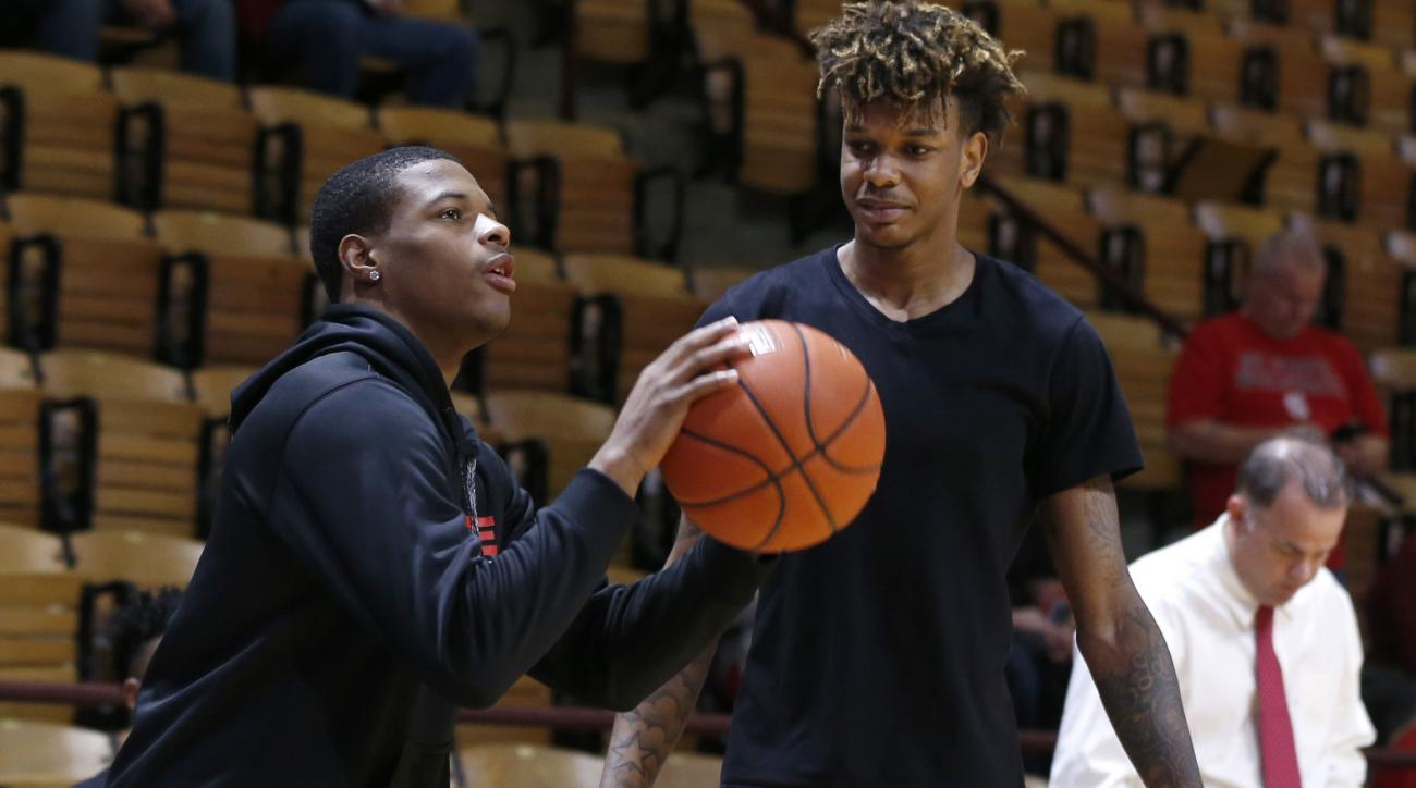 In this photo taken Jan. 2, 2016, North Carolina State's Dennis Smith Jr., left, shoots as Shaun Kirk watches during warmups before the Wolfpack's game against Virginia Tech at Cassell Coliseum in Blacksburg, Va. While his teammates head into Saturday's g