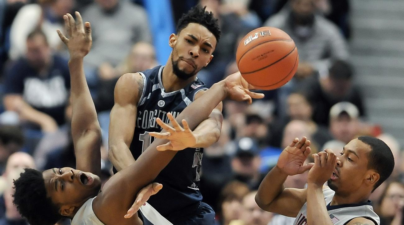 Connecticut's Steven Enoch, left, stops a drive to the basket by Georgetown's Isaac Copeland, center, as Connecticut's Omar Calhoun, right, defends, in the first half of an NCAA college basketball game, Saturday, Jan. 23, 2016, in Hartford, Conn. (AP Phot