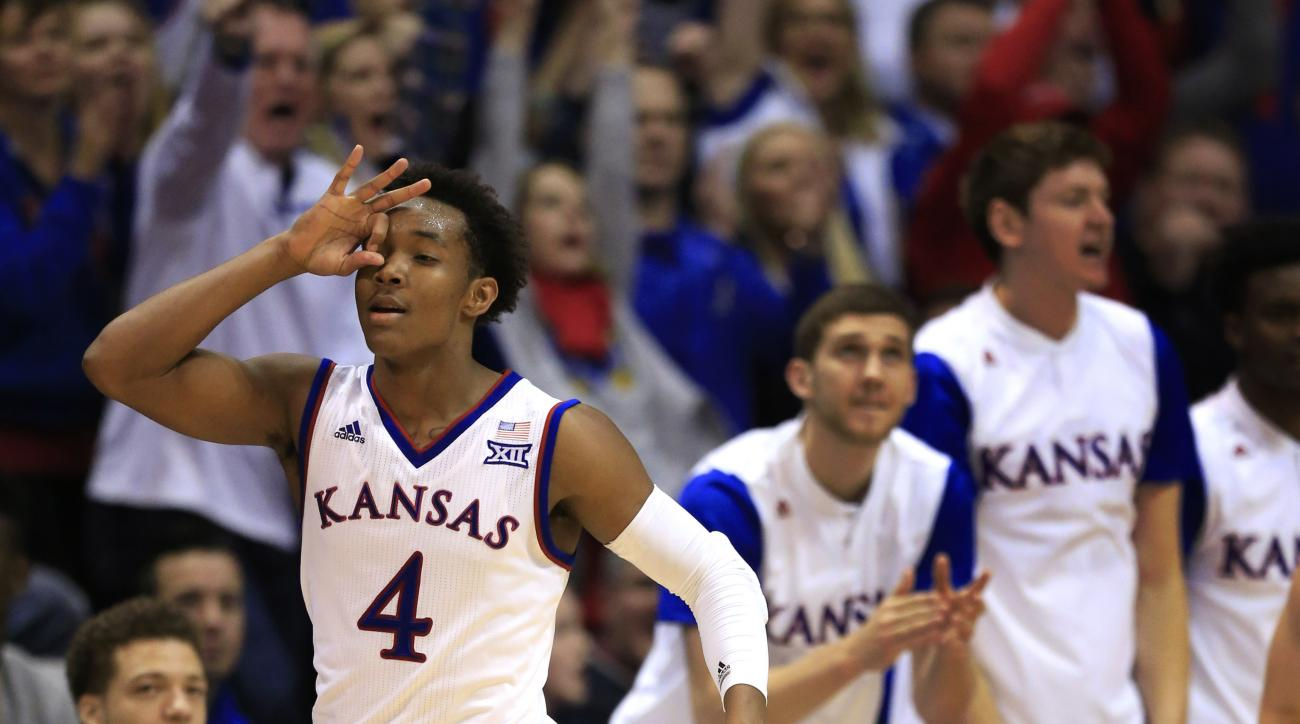 Kansas guard Devonte' Graham (4) celebrates a 3-point basket during the second half of an NCAA college basketball game against Texas in Lawrence, Kan., Saturday, Jan. 23, 2016. Kansas defeated Texas 76-67. (AP Photo/Orlin Wagner)