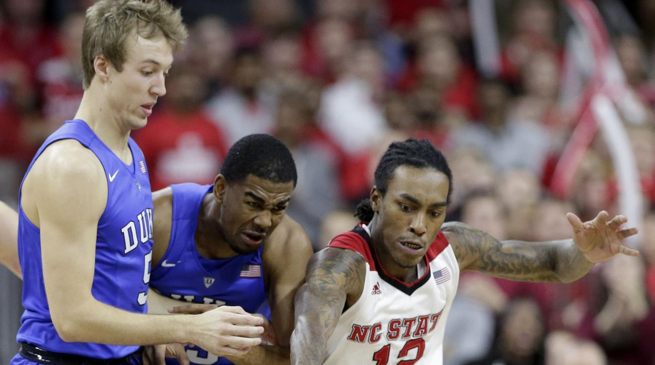 Duke's Luke Kennard, left, and Matt Jones chase the ball with North Carolina State's Anthony Barber (12) during the first half of an NCAA college basketball game in Raleigh, N.C., Saturday, Jan. 23, 2016. Duke won 88-78. (AP Photo/Gerry Broome)