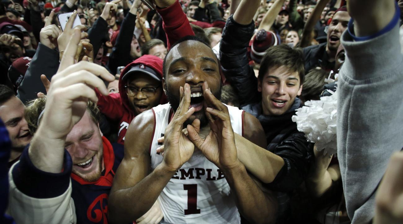 Temple's Josh Brown celebrates with students who stormed the court after Temple upset SMU, 89-80, in an NCAA college basketball game, Sunday, Jan. 24, 2016, in Philadelphia. (AP Photo/Matt Slocum)