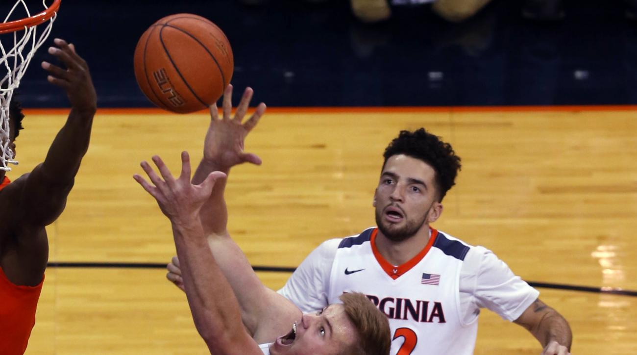 Virginia center Jack Salt (33) grabs the rebound in front of Syracuse center DaJuan Coleman (32) during an Atlantic Coast Conference basketball game, Sunday Jan. 24, 2016, in Charlottesville, Va. (Photo/Andrew Shurtleff)