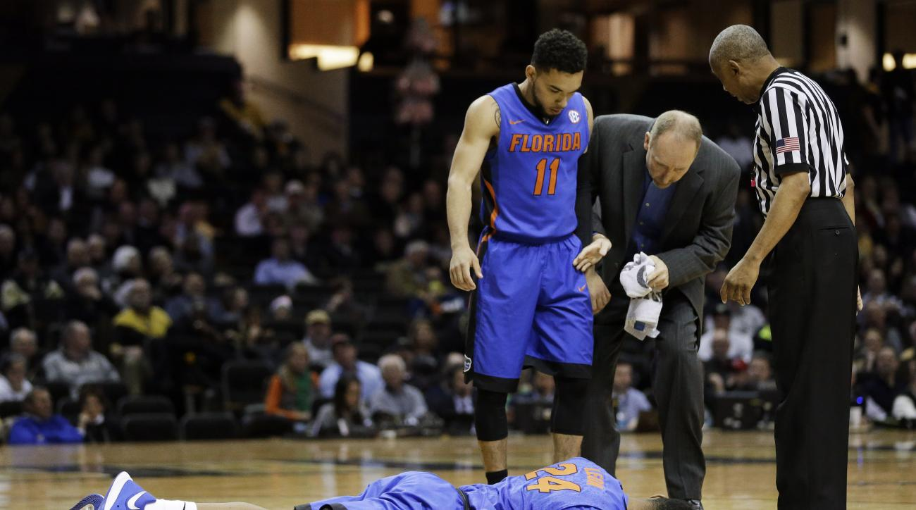 Florida forward Justin Leon (24) lies on the court after being injured in the first half of an NCAA college basketball game against Vanderbilt Tuesday, Jan. 26, 2016, in Nashville, Tenn. Florida guard Chris Chiozza (11) looks on. (AP Photo/Mark Humphrey)