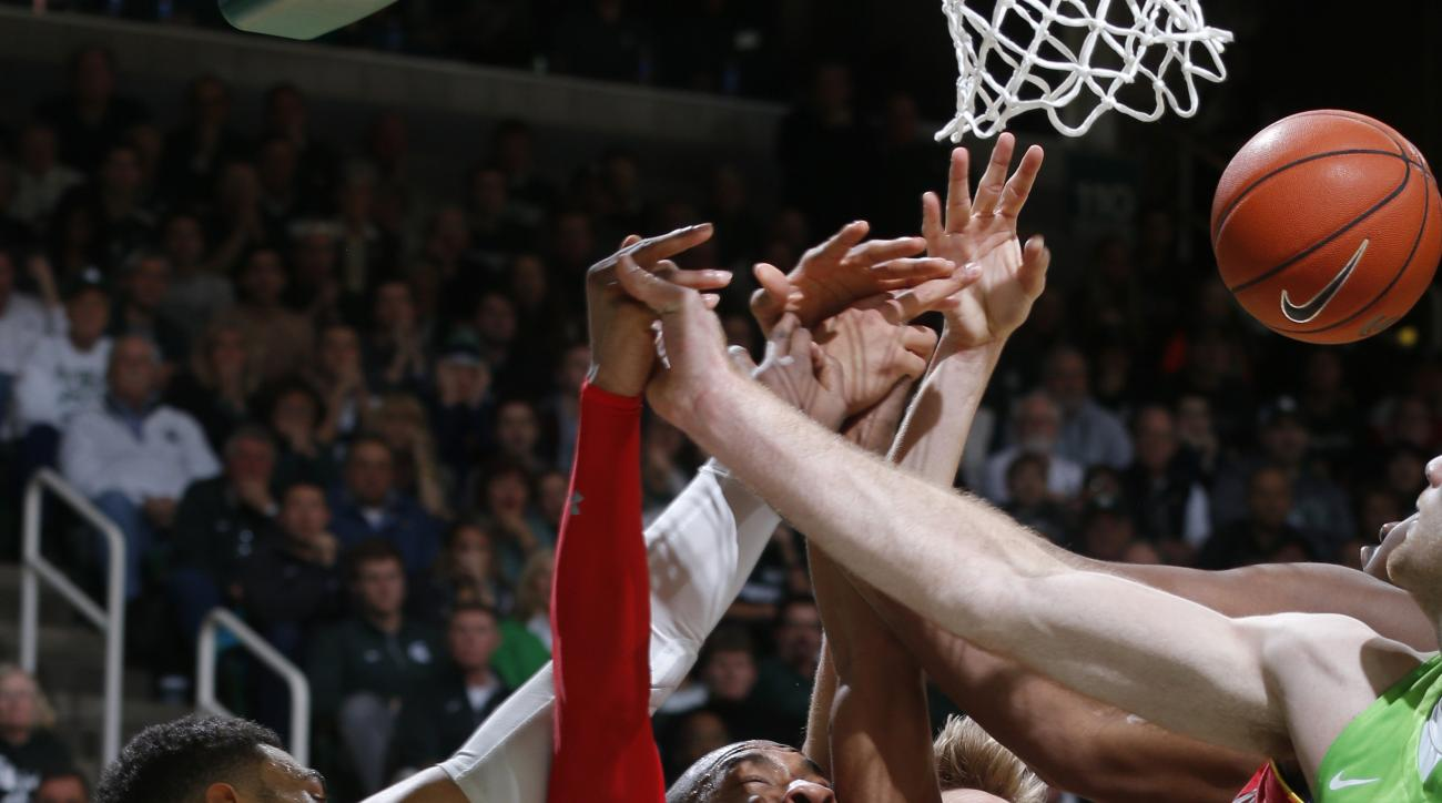 FILe - In this Jan. 23, 2016, file photo, Michigan State's Denzel Valentine (45), Maryland's Rasheed Sulaimon (0) and Jake Layman, rear, and Michigan State's Matt Costello, right, vie for a rebound during the second half of an NCAA college basketball game