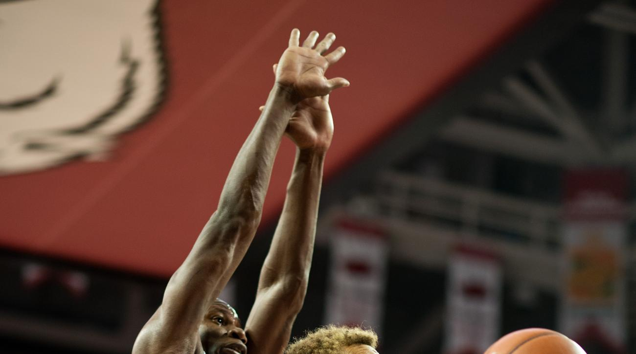 Texas A&M's DJ Hogg (1) shoots a basket as Arkansas' Moses Kingsley (33) defends in the second half of an NCAA college basketball game in Fayetteville, Ark., Wednesday, Jan. 27, 2016. Arkansas won 74-71. (AP Photo/Sarah Bentham)