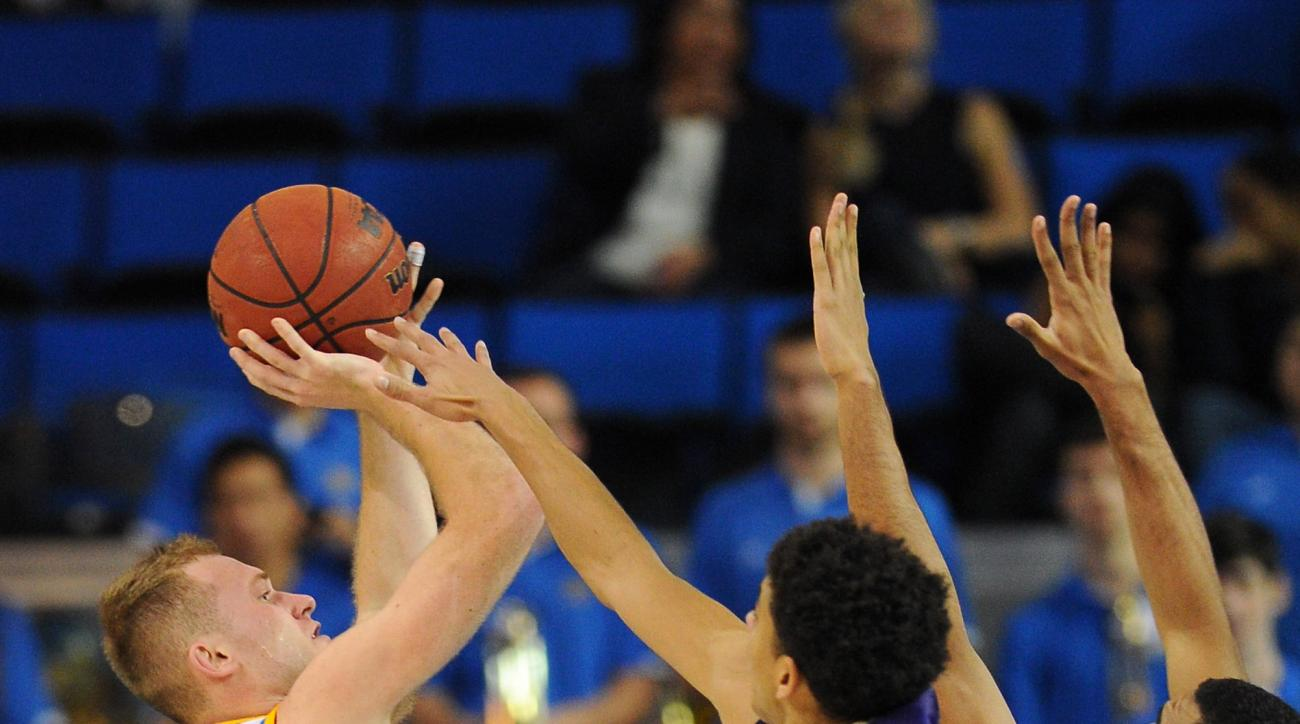 UCLA's Bryce Alford, left, shoots under pressure from Washington's Matisse Thybulle and Devenir Duruisseau, right, in the first half of an NCAA college basketball game in Los Angeles, Thursday, Jan. 28, 2016. (AP Photo/Michael Owen Baker)