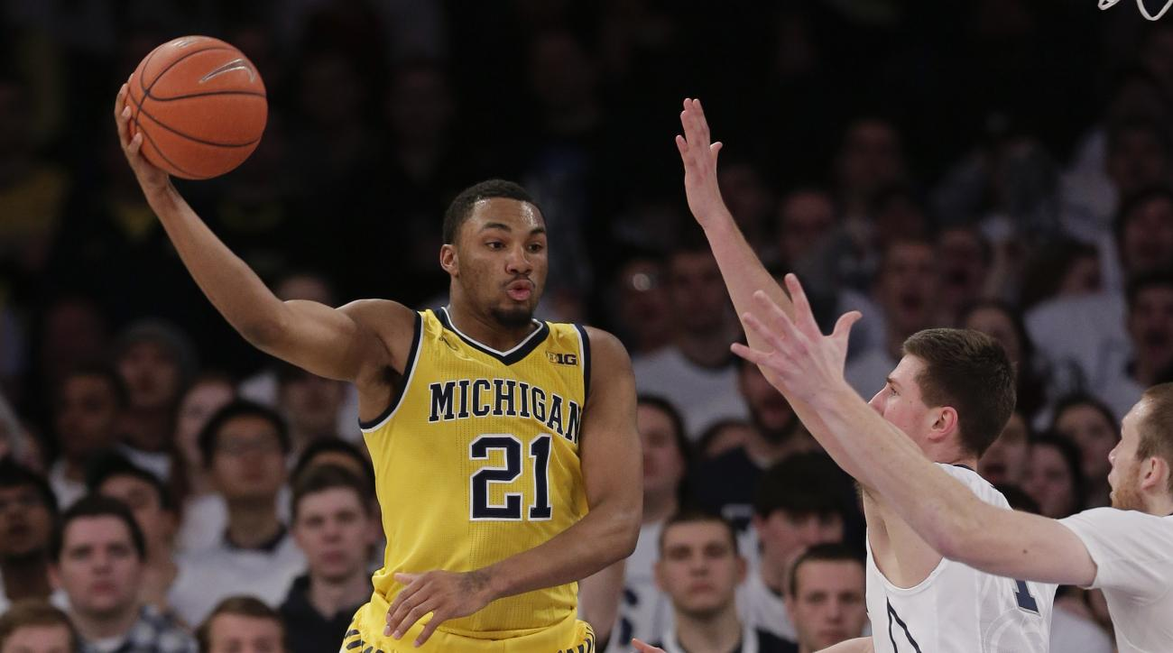 Michigan guard Zak Irvin (21) passes the ball against Penn State defenders during the first half of an NCAA college basketball game, Saturday, Jan. 30, 2016, at Madison Square Garden in New York. (AP Photo/Julie Jacobson)