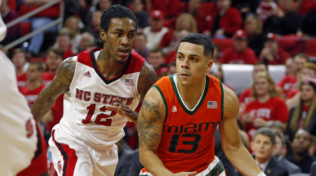 Miami's Angel Rodriguez (13) dibbles the ball past North Carolina State's Anthony Barber (12) during the first half of an NCAA college basketball game in Raleigh, N.C., Saturday, Jan. 30, 2016. (AP Photo/Karl B DeBlaker)