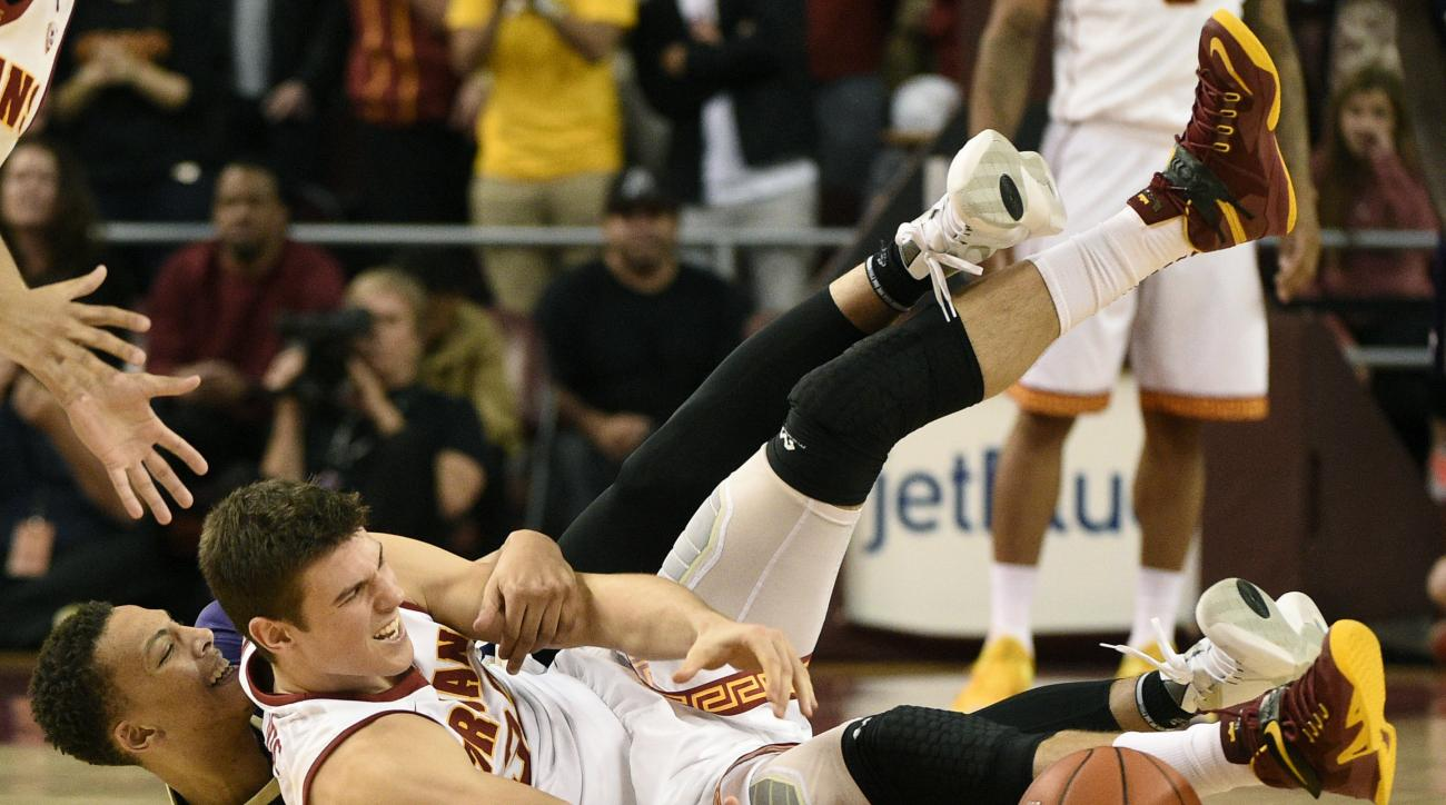 Washington forward Dominic Green, left, and Southern California forward Nikola Jovanovic, right, battle for a loose ball during the second half of an NCAA college basketball game in Los Angeles, Saturday, Jan. 30, 2016. Southern California won 98-88. (AP
