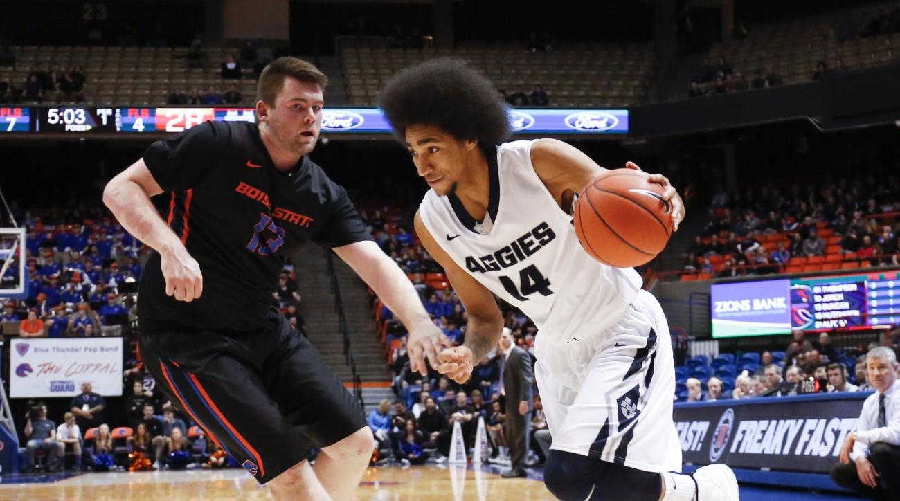 Utah State's Jalen Moore (14) drives the ball against Boise State's Nick Duncan during the first half of an NCAA college basketball game in Boise, Idaho, on Tuesday, Feb. 2, 2016. (AP Photo/Otto Kitsinger)
