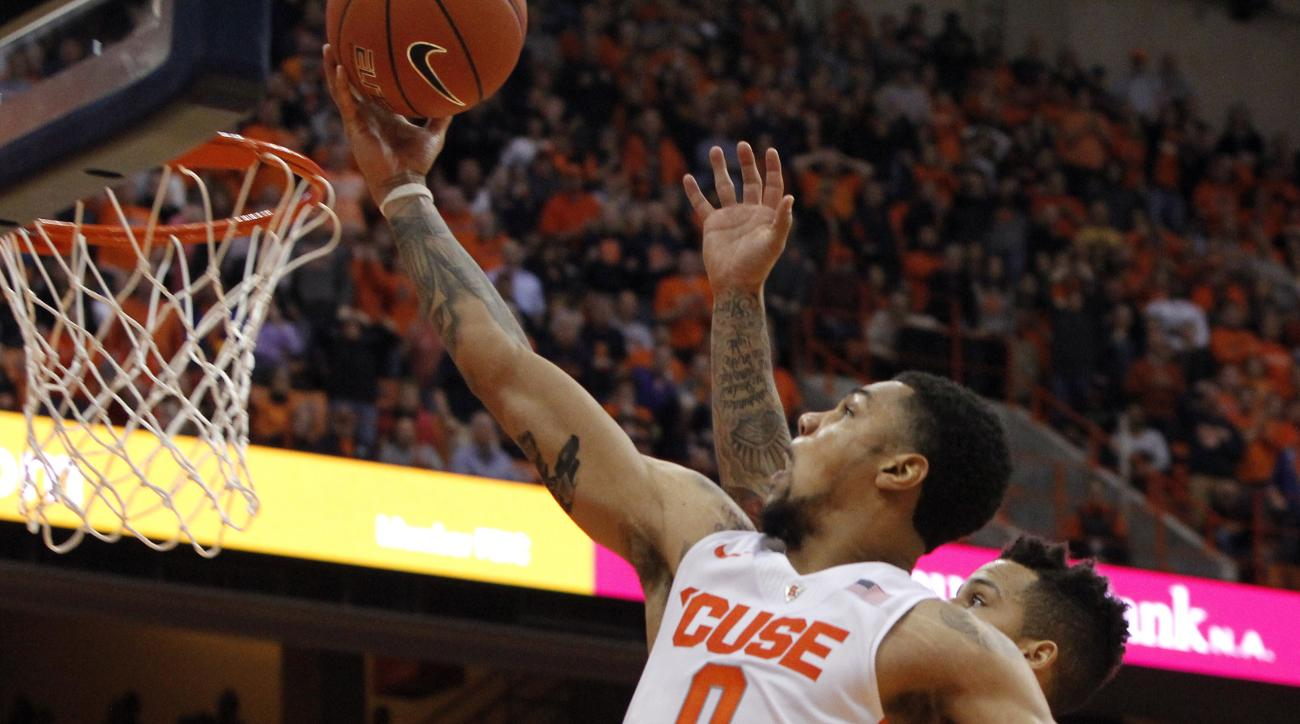 Syracuse's Michael Gbinije, left, shoots past Virginia Tech's Seth Allen, right, in overtime of an NCAA college basketball game in Syracuse, N.Y., Tuesday, Feb. 2, 2016. Syracuse won 68-60. (AP Photo/Nick Lisi)