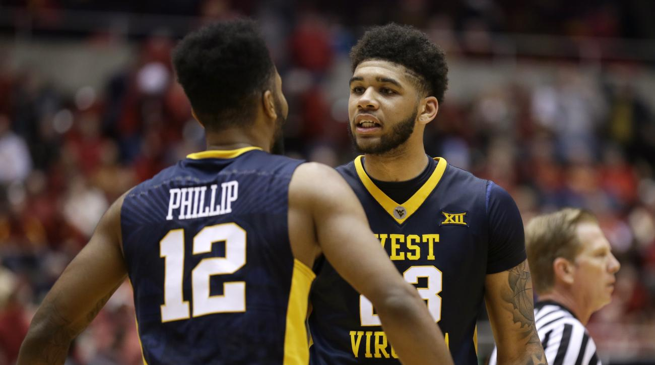 West Virginia forward Esa Ahmad, right, celebrates with teammate Tarik Phillip during the second half of an NCAA college basketball game against Iowa State, Tuesday, Feb. 2, 2016, in Ames, Iowa. West Virginia won 81-76. (AP Photo/Charlie Neibergall)