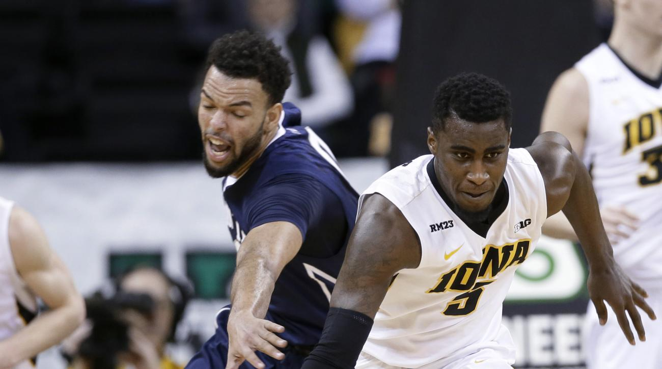 Iowa guard Anthony Clemmons brings the ball up ahead of Penn State forward Payton Banks, left, during the first half of an NCAA college basketball game Wednesday, Feb. 3, 2016, in Iowa City, Iowa. (AP Photo/Charlie Neibergall)